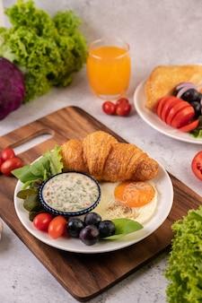 Śniadanie składa się z rogalika, jajka sadzonego, sosu sałatkowego, czarnych winogron i pomidorów.
