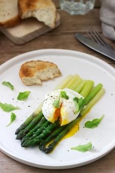 Śniadanie składające się z jajka w koszulce i gotowanych szparagów z masłem i sałatą na drewnianej powierzchni. styl rustykalny.
