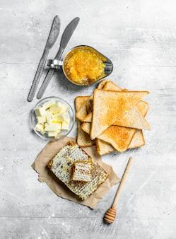 Śniadanie. tosty, miód z konfiturą pomarańczową i masłem. na rustykalnej powierzchni.