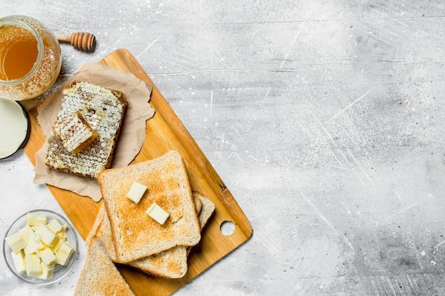 Śniadanie. tosty z masłem i miodem. na rustykalnej powierzchni.