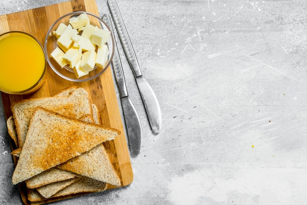 Śniadanie. tosty z masłem i szklanką soku pomarańczowego. na rustykalnym.