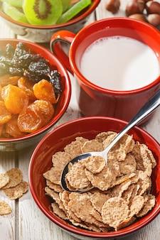 Śniadanie. trzy miseczki z suszonymi morelami i rodzynkami, suszone kiwi, płatki zbożowe z mlekiem. kubek mleka. orzechy na białym stole.