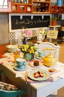 Śniadanie w kuchni z dwoma ceramicznymi kubkami z białą kawą, truskawkami i kwiatami.