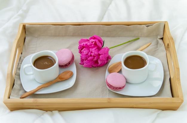 Śniadanie w łóżku dla dwóch osób. drewniana taca z kawą, makaroniki i bizet. dekoracja różowa piwonia. piękne naturalne światło z okna.