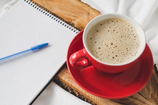 Śniadanie w łóżku i pusty notatnik na uwaga.