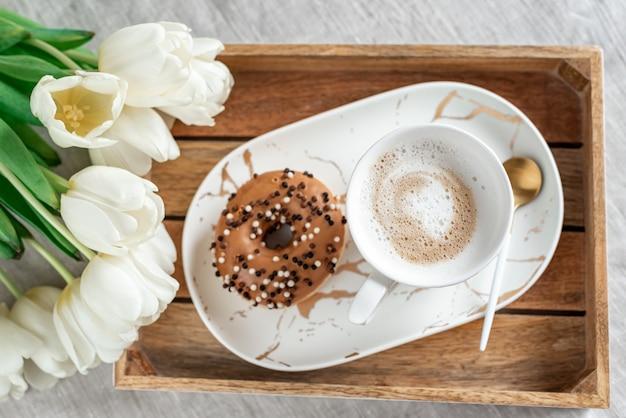 Śniadanie w łóżku z filiżanką cappuccino, pączka i białych tulipanów