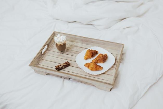 Śniadanie w łóżku z kawą i rogalikami