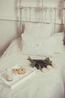 Śniadanie w łóżku z kwiatami, mlekiem i ciastkami