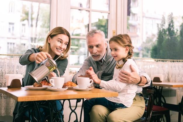 Śniadanie w stołówce. szczęśliwi dziadkowie i śliczna mała dziewczynka czują się niezapomniani jedząc śniadanie w stołówce