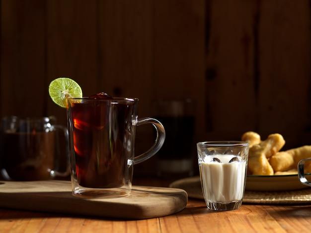 Śniadanie w stylu tajskim z cytryną, mrożoną herbatą, kawą, mlekiem i smażonymi w głębokim oleju paluszkami