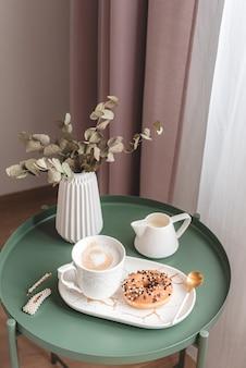 Śniadanie w sypialni z filiżanką cappuccino i pączkiem