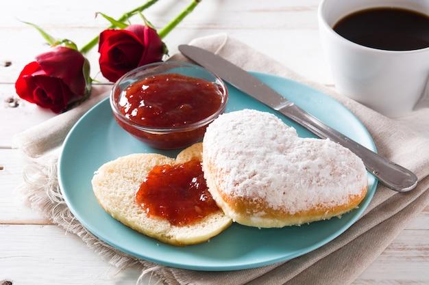Śniadanie walentynkowe z kawą, bułką w kształcie serca i konfiturą jagodową.