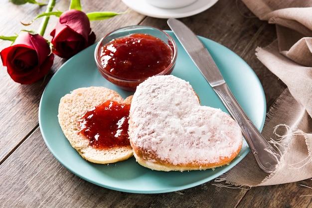 Śniadanie walentynkowe z kawą, bułką w kształcie serca, konfiturą jagodową i różami