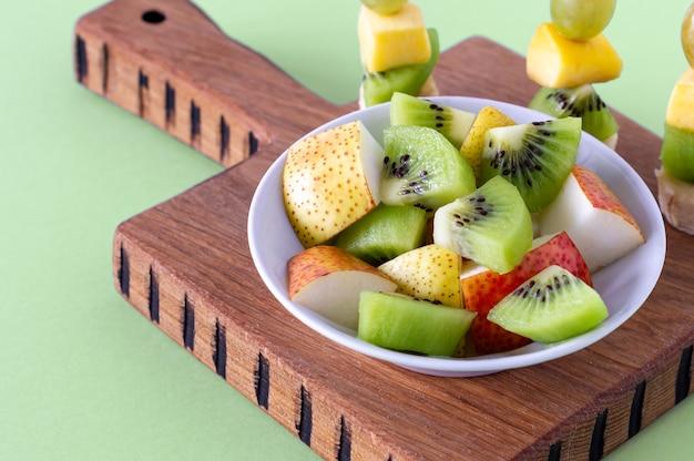 Śniadanie wegańskie. różnorodność owoców na drewnianej desce do krojenia, selektywne focus, sałatka owocowa.