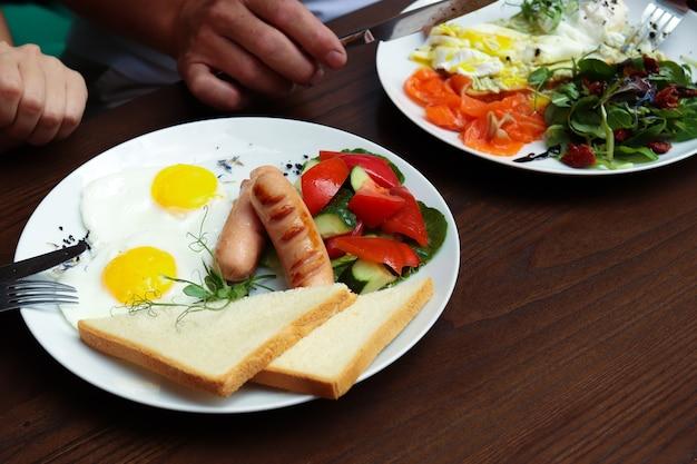 Śniadanie z bliska na talerzu, jajka z tostami i kiełbaskami.
