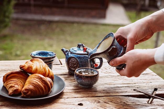 Śniadanie z chińską herbatą i świeżymi wypiekami, aromatyczne rogaliki maślane. ręce kobiet nalewają herbatę. herbaciana ceremonia.