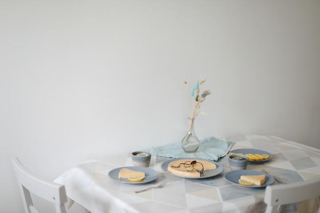 Śniadanie z ciastem cytrynowym na talerzu z zestawem do herbaty i cytrynami