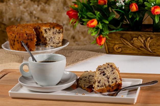 Śniadanie z ciastem pszennym, czekoladą i kawą. stół śniadaniowy z filiżanką kawy i ciastem. tło ciasto i dzbanek z kwiatami.