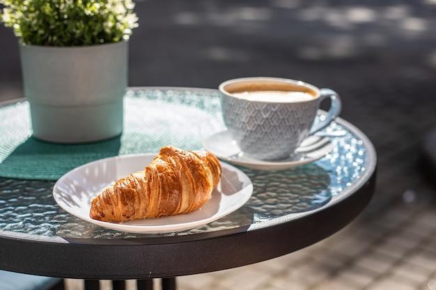 Śniadanie z croissantem i cappuccino na stole wczesnym rankiem w ulicznej kawiarni