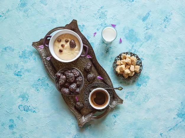 Śniadanie z datami, kawą i zdrową owsianką na niebieskim stole.