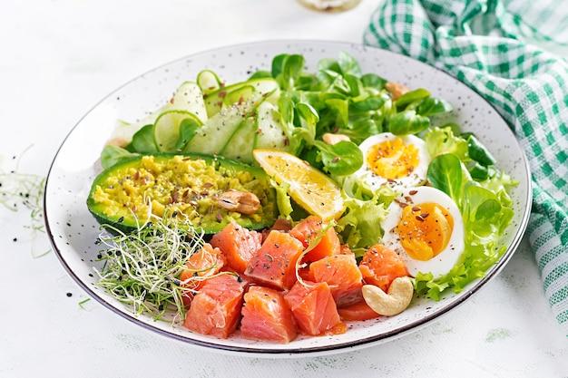 Śniadanie z dietą ketogeniczną. sałatka z solonego łososia z zieleniną, ogórkami, jajkiem i awokado. lunch keto / paleo.