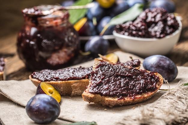 Śniadanie z domowego chleba z powidłami śliwkowymi i świeżych dojrzałych śliwek.