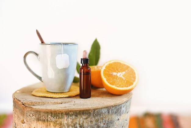 Śniadanie z filiżanką herbaty, świeżą pomarańczą i pipetą do dodania kropli medycyny alternatywnej