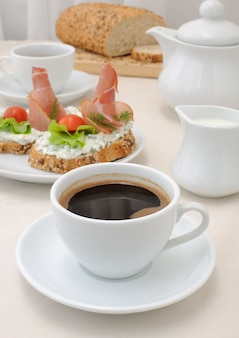 Śniadanie z filiżanką kawy i kanapką z pełnoziarnistego pieczywa z ricottą i szynką