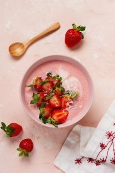 Śniadanie z granolą, kokosem i truskawkowym smoothie w misce na różowej jasnej ścianie. wiosenne menu dietetyczne. widok z góry.