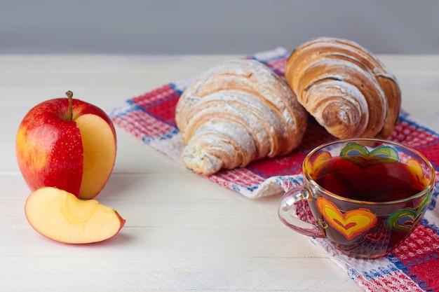 Śniadanie z herbatą, rogalikiem i jabłkiem