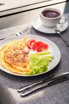 Śniadanie z jajecznicą z pomidorami i ogórkami oraz herbatą