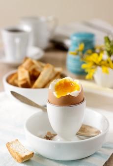 Śniadanie z jajka na miękko, tostów chlebowych, kawy ze śmietaną i świeżej gazety.