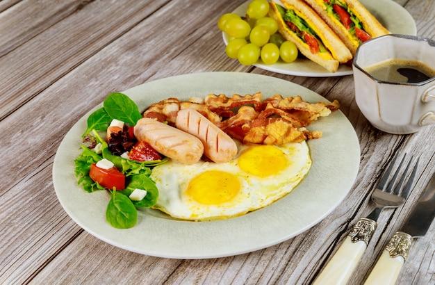 Śniadanie z jajkami, kiełbasami, boczkiem i filiżanką kawy