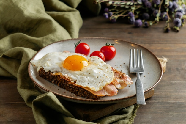 Śniadanie z jajkiem, boczkiem i pomidorami