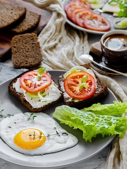 Śniadanie z jajkiem sadzonym, tostem z serem, sałatą, pomidorami i przyprawami oraz filiżanką kawy