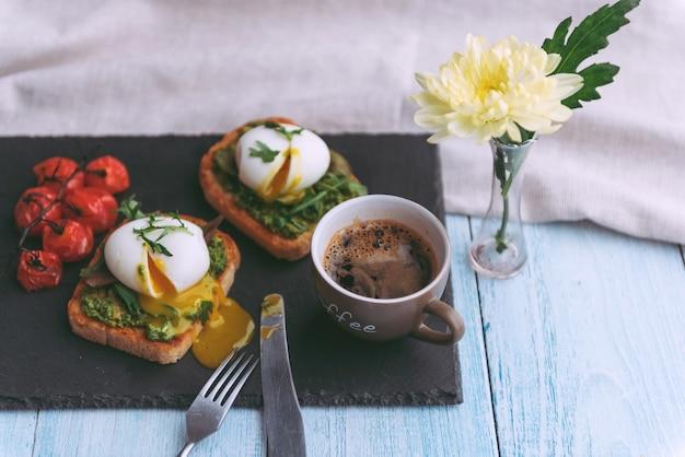 Śniadanie z jajkiem w koszulce na łopatce z awokado i bazylią oraz filiżanka kawy