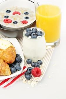 Śniadanie z jogurtem, sokiem pomarańczowym, jagodami i croissantem