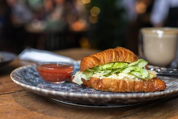 Śniadanie z kanapką croissant z serem i sałatką podawane z sosem pomidorowym