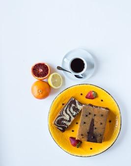 Śniadanie z kawą i herbatą z różnymi wypiekami i owocami na białym drewnianym stole