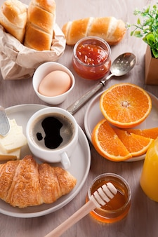 Śniadanie z kawą, sokiem pomarańczowym i rogalikiem. widok z góry