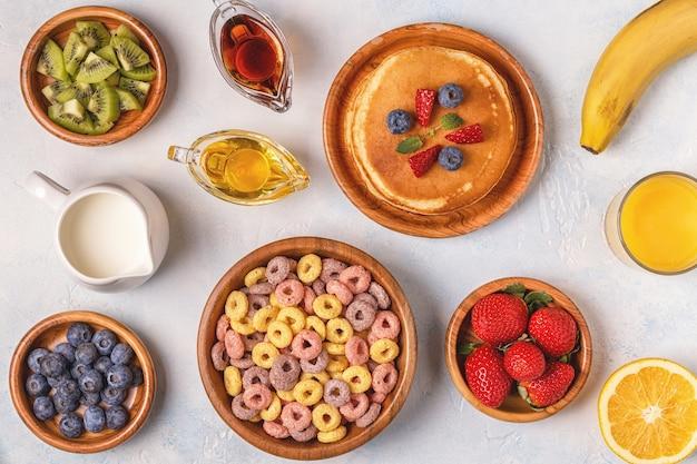 Śniadanie z kolorowymi krążkami zbożowymi, naleśnikami i sokiem pomarańczowym