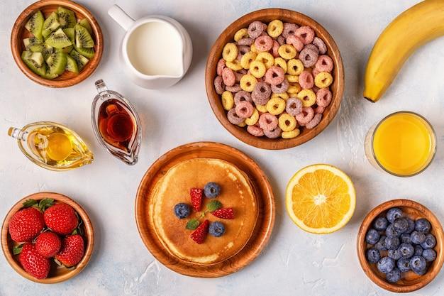 Śniadanie z kolorowymi krążkami zbożowymi, naleśnikami, owocami, mlekiem, sokiem