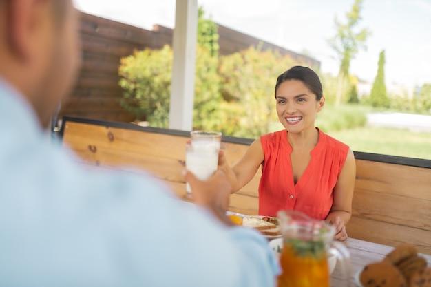 Śniadanie z mężem. piękna żona uśmiechnięta podczas śniadania z mężem w weekend?
