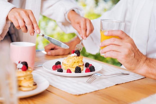 Śniadanie z naleśnikami. dojrzały mężczyzna ma ładne ciepłe naleśniki z miodem i jagodami na śniadanie i szklankę soku pomarańczowego