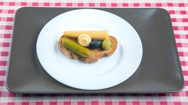 Śniadanie z oliwek konserwowych i marynowanych, pieczarki ogórkowe z pieczywem na białym talerzu. żywność i warzywa. dieta i utrata masy ciała