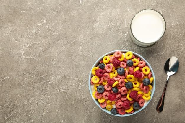 Śniadanie z płatkami kukurydzianymi, mlekiem i jagodami na szarym tle. widok z góry. zdjęcie pionowe