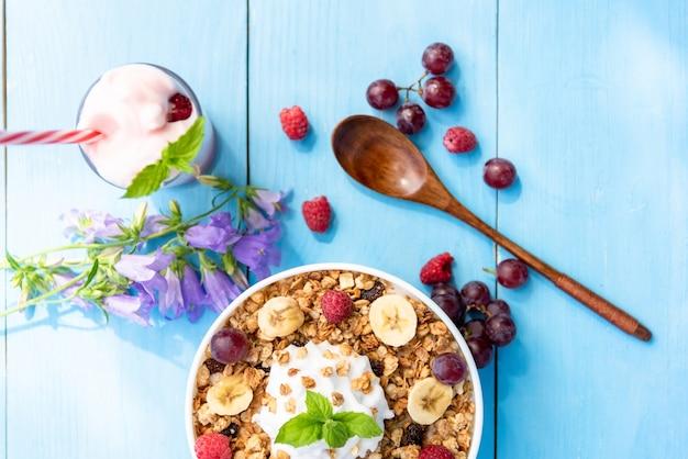 Śniadanie z płatkami zbożowymi z malinami, winogronami, bananem i szklanką jogurtu jagodowego ze słomką