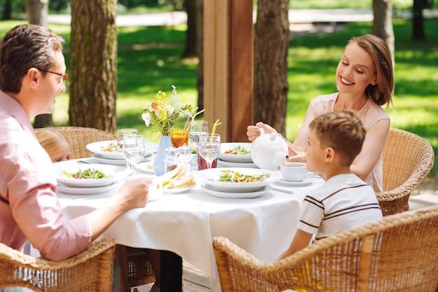 Śniadanie z rodzicami. mały jasnowłosy synek je śniadanie z rodzicami siedząc przed domem jednorodzinnym