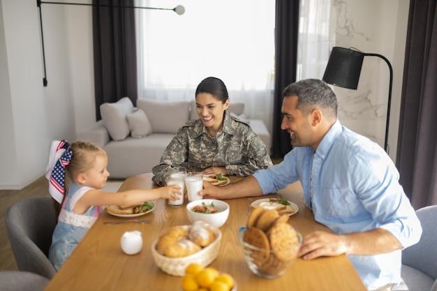 Śniadanie z rodziną. rozpromieniona szczęśliwa wojskowa kobieta uśmiecha się szeroko podczas śniadania z rodziną