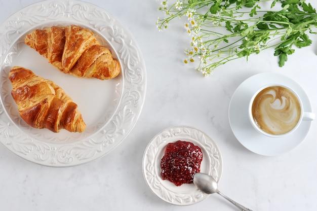 Śniadanie z rogalikami, dżemem malinowym i cappuccino